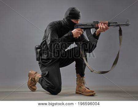 man in black military uniform shooting with a machine gun