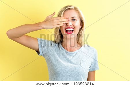 Happy young woman covering one eye with her hand on a bright yellow background