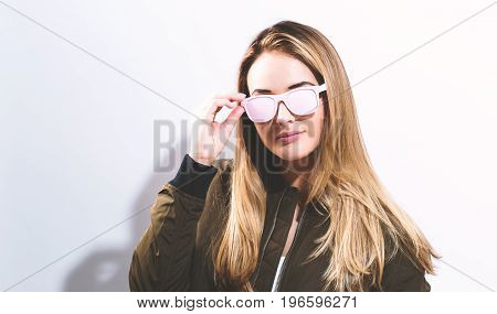 Hipster girl wearing sunglasses on a white background
