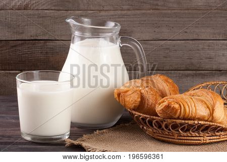 jug and glass of milk with croissants on a wooden background.