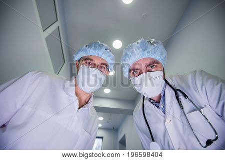 Surgeons standing above of the patient before surgery.