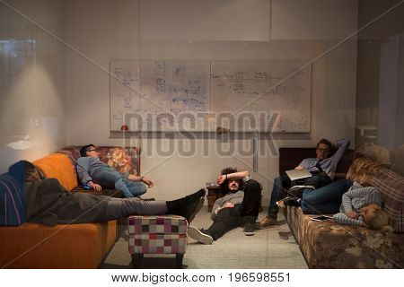 group of young casual software developer sleeping on  sofa during a work break in creative startup office