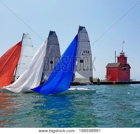 red white and blue spinnakers on sailboat in Holland Harbor channel with red lighthouse