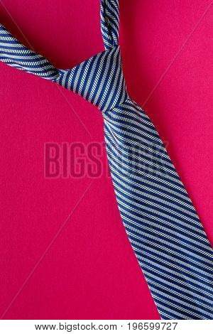 Classic blue striped tie on red background. Man style concept