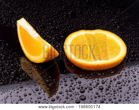 Healthy orange fruit slices on a black surface with reflection and water droplets