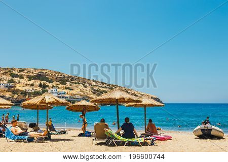 Crete Island, Greece, June 09, 2017: Panorama Of Matala Beach. Caves On The Rocks Were Used As A Rom