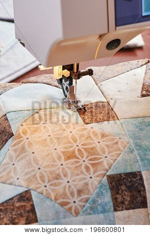 Modern sewing machine working on a patchwork block of quilt
