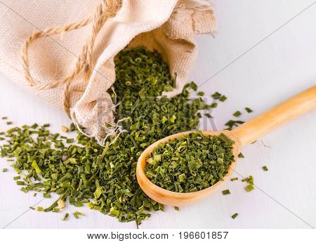 Baggy sack with dried green spices and a wooden spoon on a white kitchen table