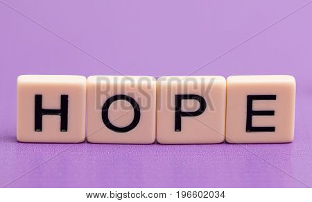 Hope Spelled Out in Tiles on a Purple Background