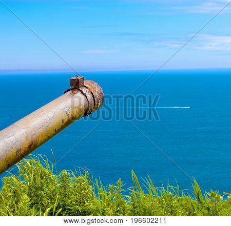 trunk of an old rusty military weapon on the coast of Kamchatka