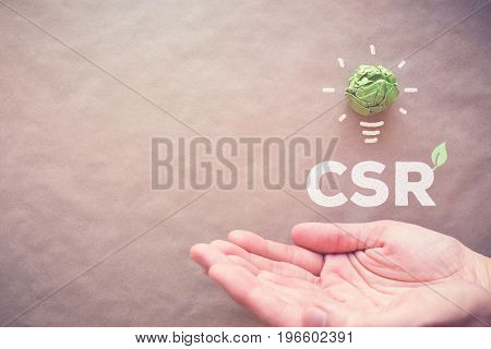Green paper light bulb with CSR over hands Corporate social responsibility