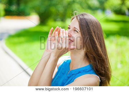 Young beautiful brunette woman shouts toward covering his face with his hand in summer park