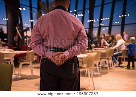 Rear view of young confident waiter standing with hands behind his back in a luxury restaurant