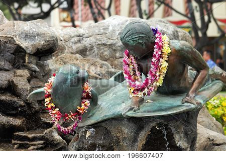 Honolulu Hawaii USA - May 28 2016: Makua and Kila bronze statue - public art sculpture shows a young surfer (Makua) sharing a moment with a monk seal (Kila).