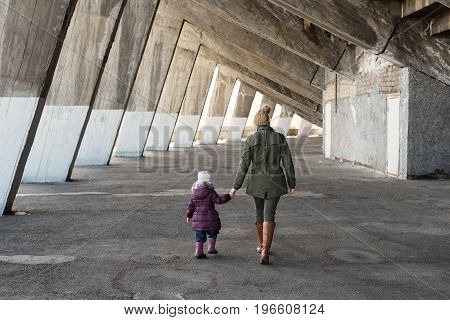 Mother and daughter walking hand in hand in an old massive grunge constraction.