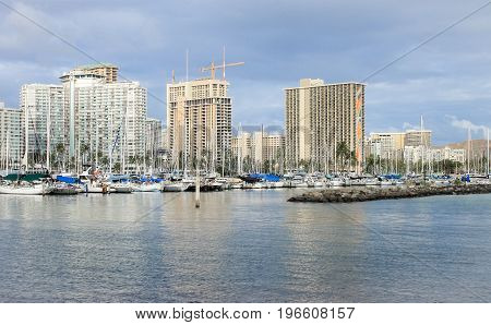 Honolulu Hawaii USA - May 30 2016: Yachts docked at Ala Wai Boat Harbour in the Kahanamoku Lagoon with high rise buildings in the background