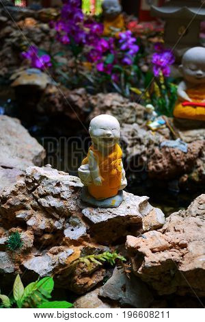 a little smiliing monk statue in a garden