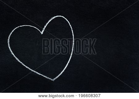 Heart shape written in white chalk on blackboard