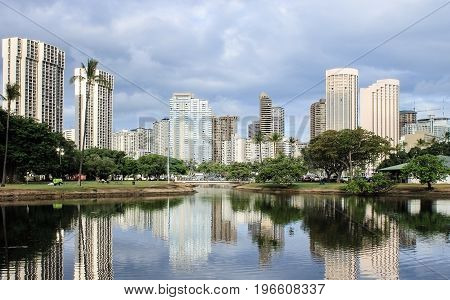 Honolulu, Hawaii, USA - May 30, 2017: Buildings reflecting upon the lagoon at Ala Moana Beach.