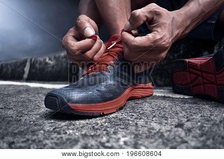 Man tying running shoes on asphalt road