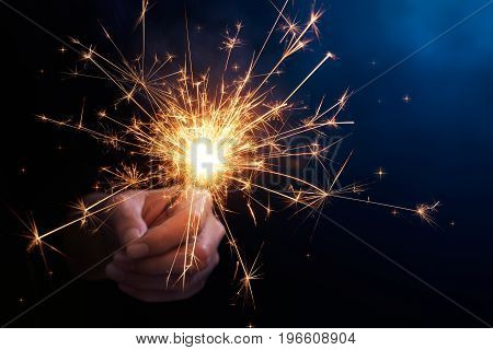 Close-up of hand holding a sparkler on blue background