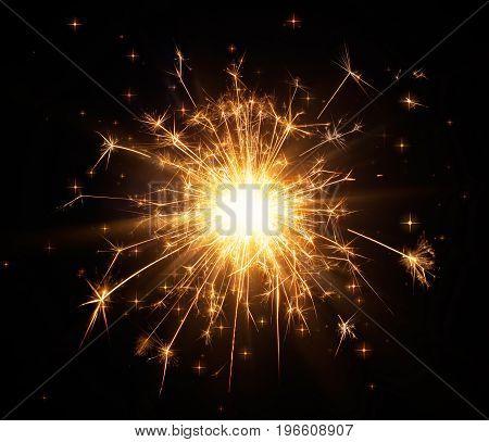 Close-up of glittering sparkler on black background