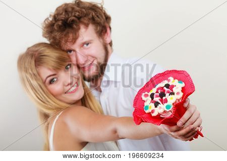Happy loving couple with candy bunch bouquet flowers. Handsome man and pretty woman holding present gift. Love concept.