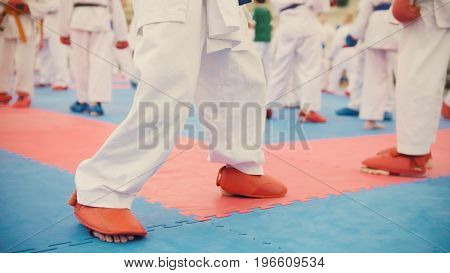 Karate training - group of karateka teenagers in red shoes and white kimono, close up