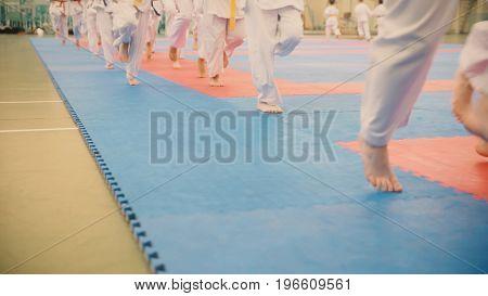 Group of karateka teenagers in kimono runs on tatami in the gym, close up