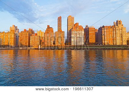 Scenic urban landscape along East River in Manhattan New York. Buildings reflection in East River at sunrise.