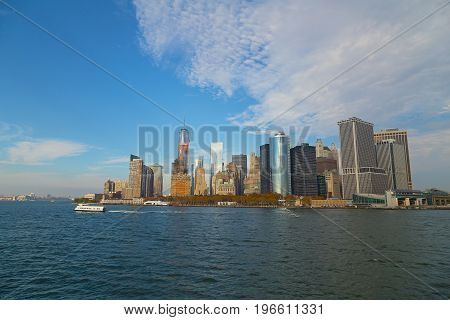 Panorama of Lower Manhattan from the water in fall New York USA. Financial district architectural landmarks before sunset.