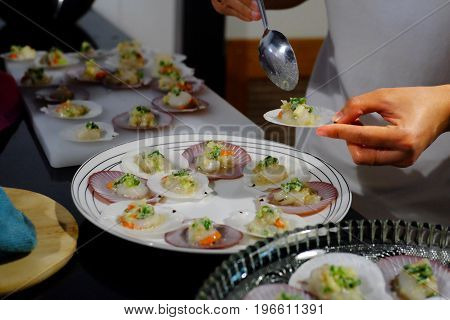 Female hands scallops topped with butter garlic and parsley preparing grill. In the kitchen