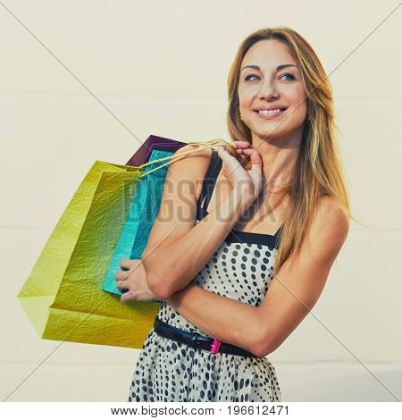 Portrait of smiling glad woman holding paperbags after shopping. image with toning