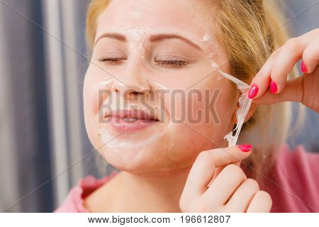 Woman Peeling Off Gel Mask From Face