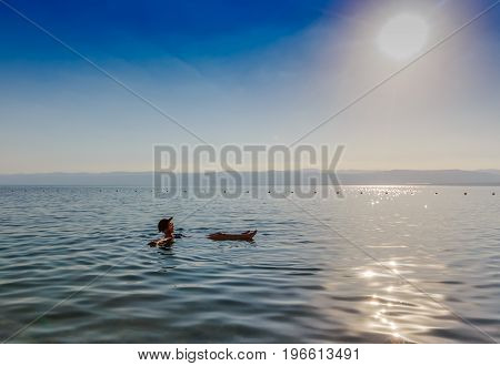 Girl floating on surface of Dead Sea Jordan enjoy her vacation during sunset time in summer. Concept for holiday travel lifestyle and wellness.