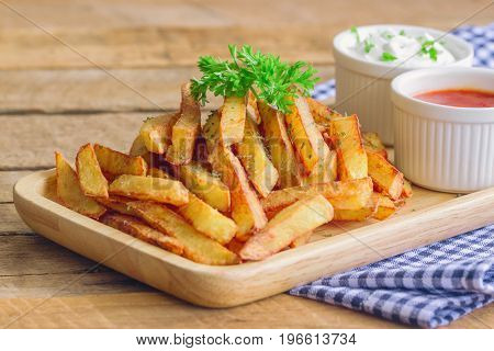 Homemade french fries serve with ketchup and sour cream or mayonnaise. Golden brown crispy french fries sprinkle with salt and oregano on wood plate for snack or appetizer. French fries on wood table ready to served with dipping sauce.