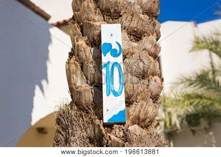 Number ten 10 painted on wooden signboard.