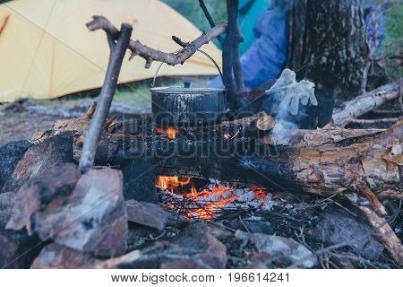 Pot on the fire on the background of the tent in the summer