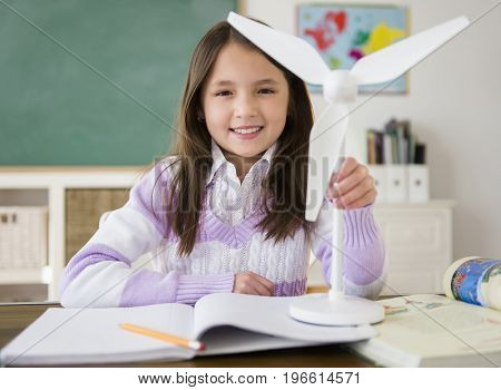 Mixed race girl holding model wind turbine in class