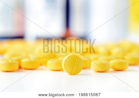 Heap of small yellow tablets (or pills) on white table with blur medicine bottle background