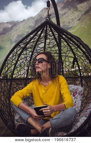 Woman reading book on digital device. Enjoy vacation. Hipster girl relaxing crossed legs and looking away in lounge hanging chair. Wicker swing. Casual style outdoor. Freelance concept. Yellow sweater