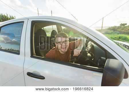 Portrait of happy smiling young man, buyer sitting in his new car and showing keys outside dealer office. Personal transportation, auto purchase concept.
