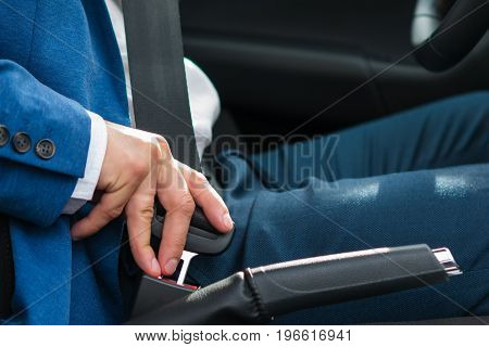 Hand of a man in a jacket close-up securing the seat belt in the car