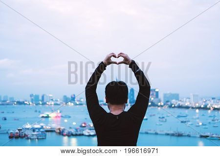 A Guy showing Heart Hand sign in evening with Bokeh lights in the City background