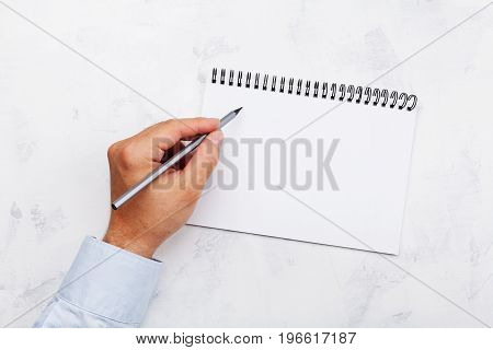 Lefty writes in empty notebook on white table top view. International Lefthanders Day.