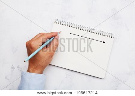 Lefty writes in notebook on white table top view. International Lefthanders Day.