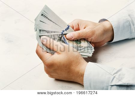 Man in shirt holding dollar money in his hands. Economy, saving, trade, salary and donate concept.