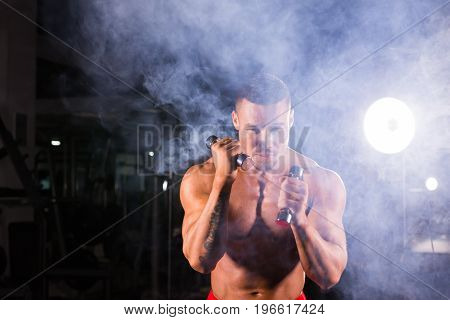 Boxing concept. Boxer man during boxing exercise making direct hit with dumbbells.