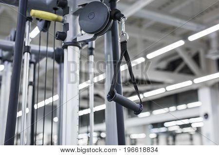 Closeup picture of hanging handle machine in a gym for pulling training.