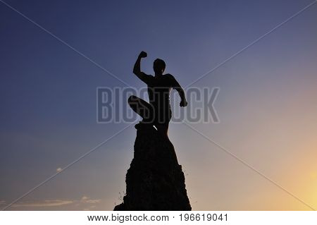 Man raised hand on top of the mountain to celebrate success. Men on the top of the steep rock